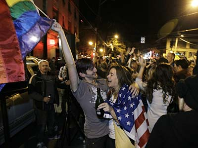 Revelers display U.S. and gay pride flags as they celebrate early election returns favoring Washington state Referendum 74, which would legalize gay marriage, during a large impromptu street gathering in Seattle´s Capitol Hill neighborhood, in the early hours of Wednesday, Nov. 7, 2012. (AP Photo/Ted S. Warren)