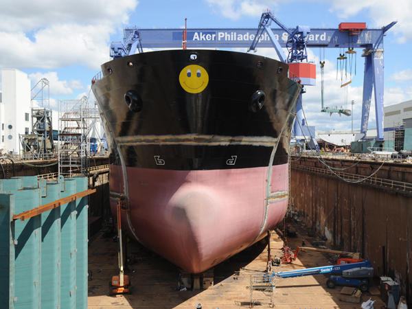 Scene from the Aker Shipbuilding complex:  Ship #18, with the Aker trademark smiley face on its bow, under construction in dry dock. (File photo: Clem Murray / Staff Photographer)