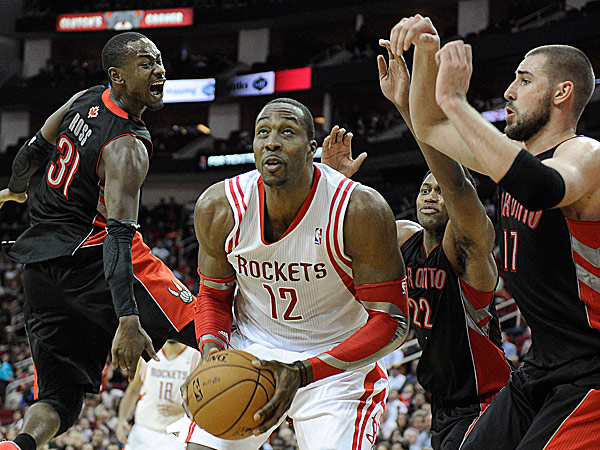 The Rockets´ Dwight Howard looks to the basket surrounded by the Raptors´ Terrence Ross, Rudy Gay and Jonas Valanciunas. (Pat Sullivan/AP)