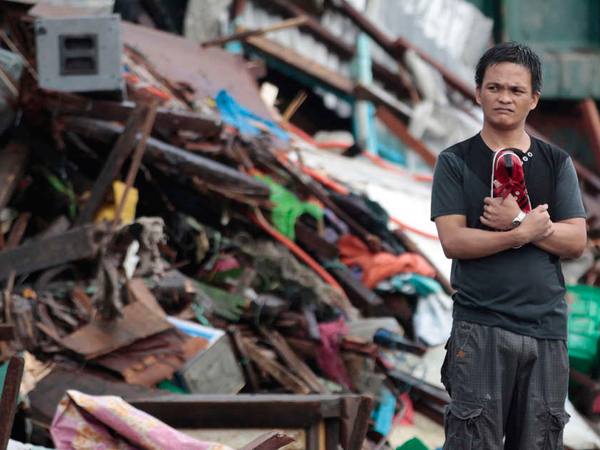 A resident surveys damage wrought by Typhoon Haiyan in the central Philippines city of Tacloban. Friday´s storm has displaced an estimated 600,000 people. AARON FAVILA / AP