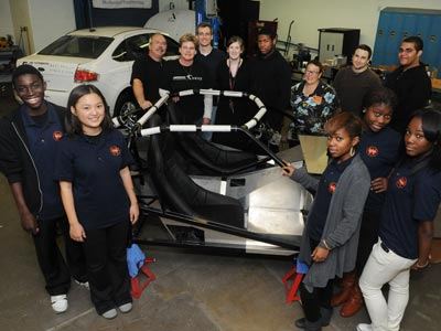 Members of the West Philly High School Automotive Academy pose with one of the energy-efficient cars they are building for competition.  (Sarah J. Glover / Staff Photographer)