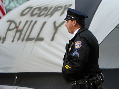 A police officer patrols the Occupy Philadelphia encampment earlier this month. (Joseph Kaczmarek/AP Photo/File)