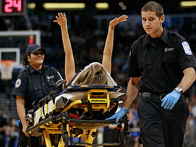 Jamie Woode, a former college cheerleader and Magic Stunt Team member, fell during a routine and is wheeled off the floor on a stretcher as she waves her arms to fans during the first half of an NBA basketball game between the Orlando Magic and the New York Knicks, Tuesday, Nov. 13, 2012, in Orlando, Fla. She was transferred to a nearby hospital. (John Raoux/AP)