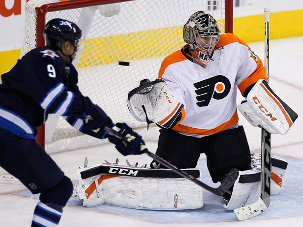 Steve Mason (35) is beaten by a slapshot from the point by Winnipeg Jets´ Dustin Byfuglien (not shown) during third-period NHL hockey game action in Winnipeg, Manitoba, Friday, Nov. 15, 2013. Jets´ Evander Kane (9) looks for the rebound. (AP Photo/The Canadian Press, John Woods)