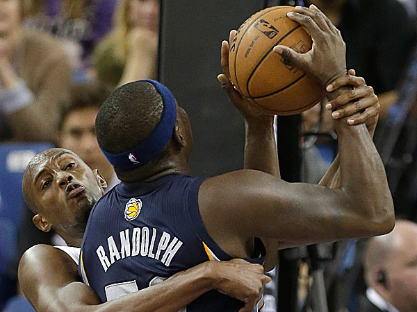 Kings forward Travis Outlaw grabs Grizzlies forward Zach Randolph as he goes to the basket. (Rich Pedroncelli/AP)