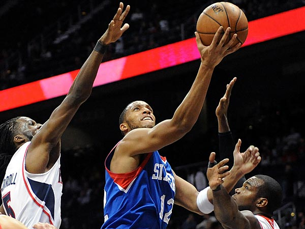 The 76ers´ Evan Turner goes up between the Hawks´ DeMarre Carroll, left, and Paul Millsap. (David Tulis/AP)