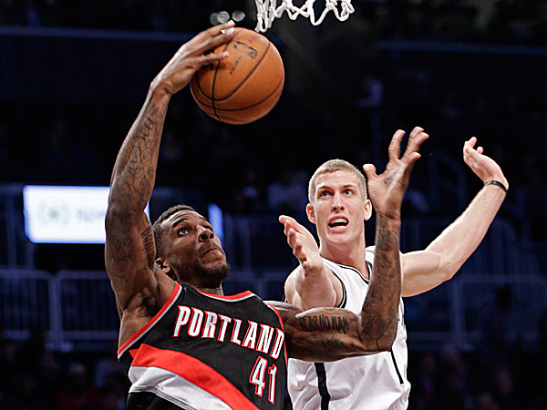 Trail Blazers power forward Thomas Robinson pulls down a rebound in front of Nets power forward Mason Plumlee. (Kathy Willens/AP)