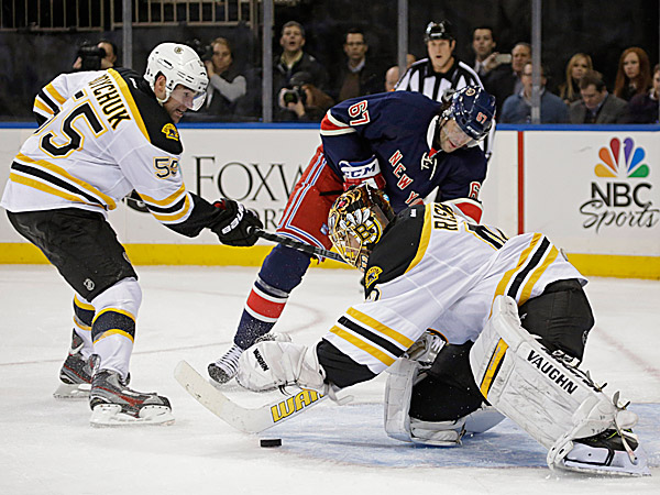 Bruins defenseman Johnny Boychuk defends as Bruins goalie Tuukka Rask makes a save with Rangers left wing Benoit Pouliot nearby. (Kathy Willens/AP)