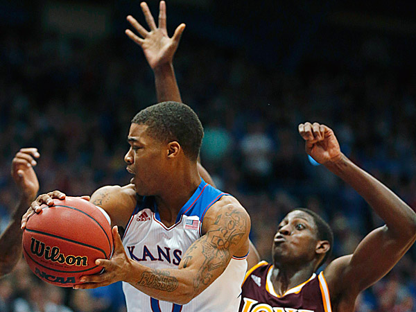 Kansas guard Frank Mason passes to a teammate while covered by Iona forward Daniel Robinson. (Orlin Wagner/AP)