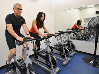 Gastroenterologist Jeff Greenspan, 56, does a spinning workout with Carrie Hubley, motivator/instructor, at Philadelphia Sports Club in Ardmore. (Sharon Gekoski-Kimmel / Staff Photographer)