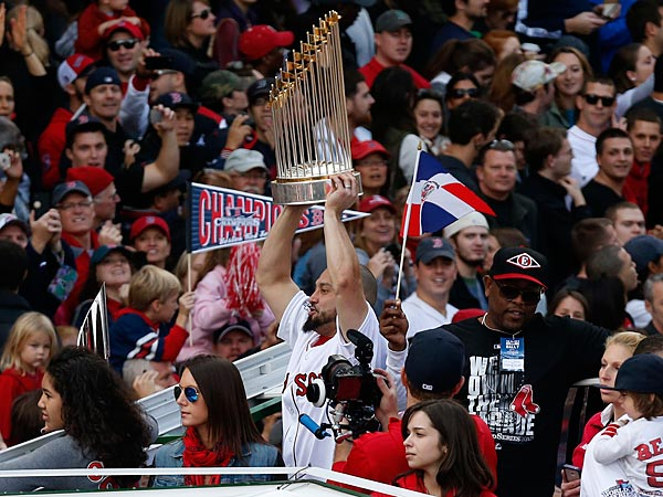 Boston Red Sox´s Shane Victorino holds the World Series trophy from on Duck Boat during a victory parade celebrating the team´s third World Series title since 2004, Saturday, Nov. 2, 2013, in Boston. (AP Photo/Michael Dwyer)