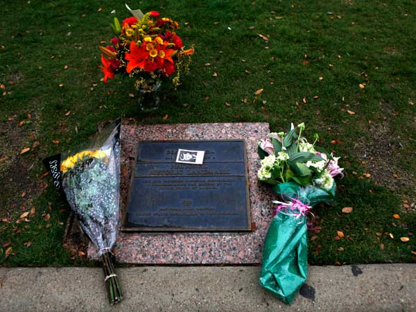 Flowers are left at the National Historic Landmark marker in Dealey Plaza in Dallas. Today is the 50th anniversary of the assassination of President John F. Kennedy. (AP Photo/The Dallas Morning News, Sarah Hoffman/)