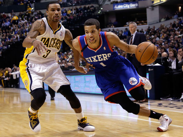 76ers guard Michael Carter-Williams dribbles around Indiana Pacers guard George Hill. (AJ Mast/AP)