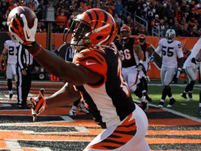 Cincinnati Bengals wide receiver Mohamed Sanu (12) catches a two-yard touchdown pass against Oakland Raiders cornerback Ron Bartell (21) in the first half of an NFL football game, Sunday, Nov. 25, 2012, in Cincinnati. (AP Photo/Tom Uhlman)