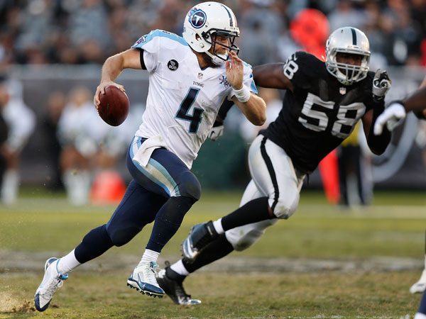 Titans quarterback Ryan Fitzpatrick (4) runs past Oakland Raiders defensive end Ryan Robinson (58) during the fourth quarter of an NFL football game in Oakland, Calif., Sunday, Nov. 24, 2013. (Beck Diefenbach/AP)