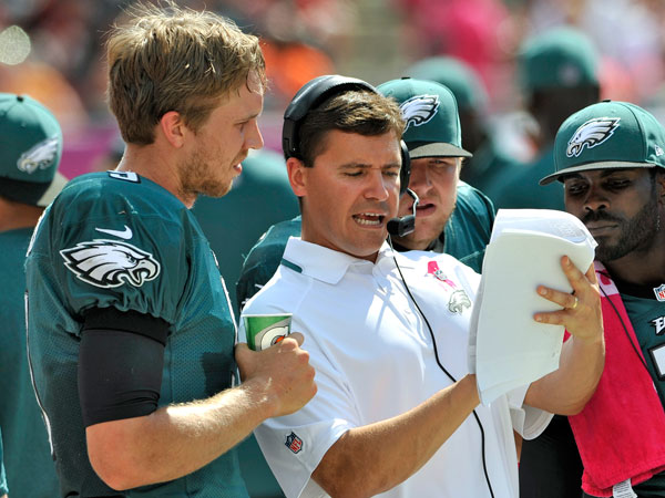 Eagles quarterbacks coach Bill Lazor, center, talks to quarterback Nick Foles, Matt Barkley and Michael Vick. (Steve Nesius/AP)