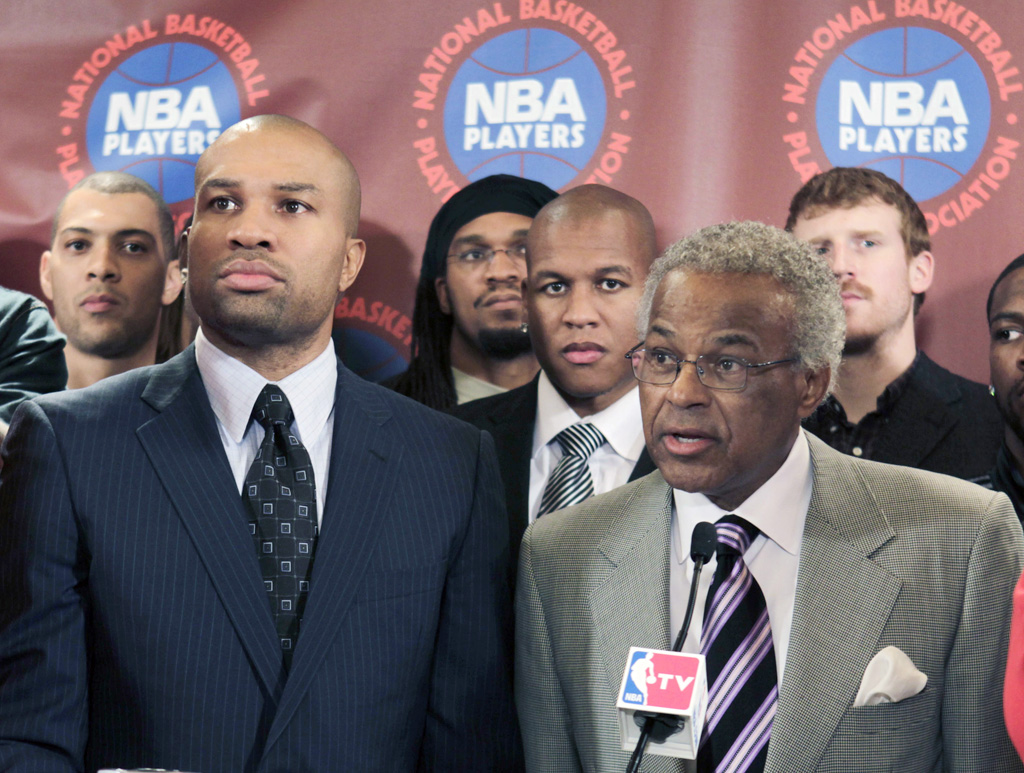 Surrounded by NBA basketball players, Billy Hunter, right, executive director of the National Basketball Players Association Billy Hunter, right, speaks to the media as Players Association president Derek Fisher, left, listens during a news conference in New York. NBA owners and players reached a tentative agreement early Saturday.  (AP Photo/Seth Wenig, File)