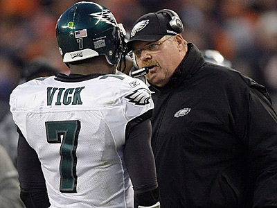 Eagles coach Andy Reid speaks with Michael Vick during the first half. (AP Photo/Charles Rex Arbogast)