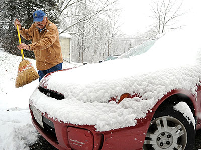 After the first snow of the season fell in the Poconos, Dieter Boehmer clears snow from his car in his driveway on Cherry Valley Road near Stroudsburg, Pa., on Tuesday, November 27, 2012. (AP Photo/Pocono Record,David Kidwell)