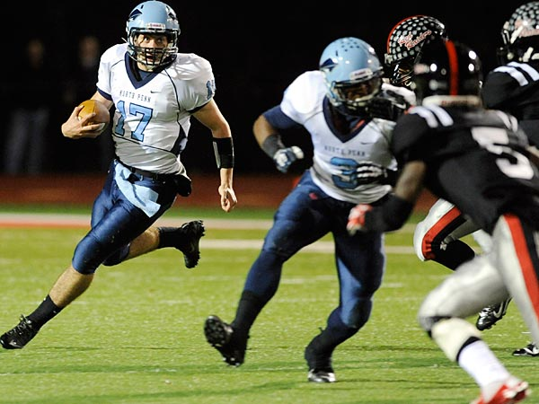 North Penn quarterback Austin Shearer, left, sprints past a host of<br />Coatesville defenders in the second quarter of play.  (Philadelphia Inquirer/Bradley C Bower)