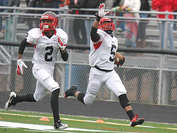Imhotep Charter´s DeAndre Scott, escorted by teammate Najee Goode, celebrates as he heads down the sideline with a second-quarter punt return. (Lou Rabito/Staff)