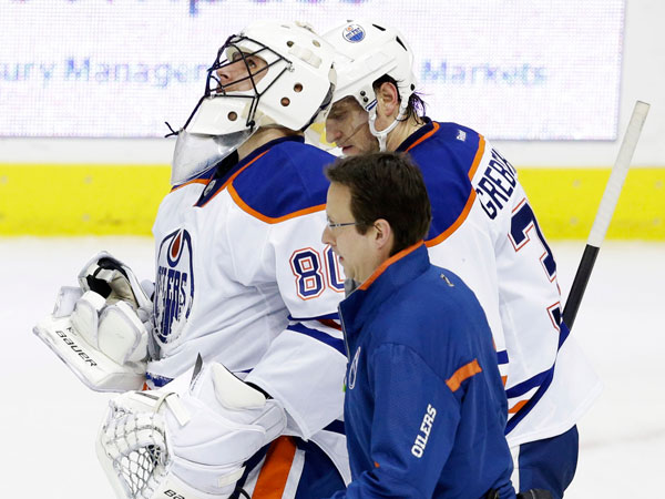 A trainer helps Edmonton Oilers goalie Ilya Bryzgalov (80) off the ice after he was hit hard during the first period of an NHL hockey game against the Dallas Stars, Sunday, Dec. 1, 2013, in Dallas. The Oilers won 3-2. (LM Otero/AP)