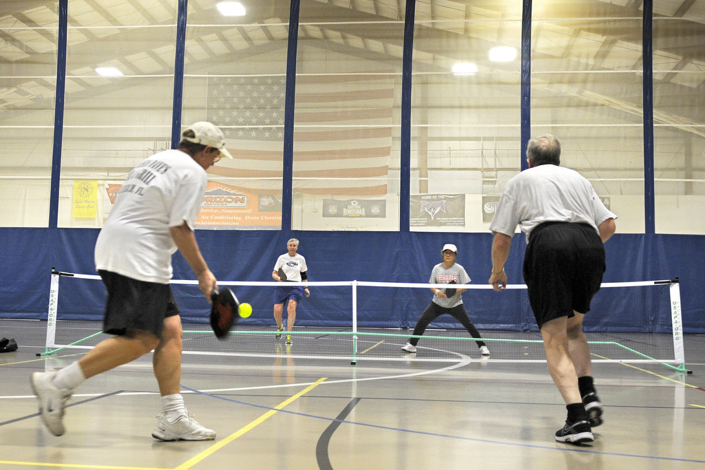 Doubles partners Judy Michel, (rear, left), 65, and Young Kang, 65, play Sue Wilson (front, left), 62, and Link Davis, 64, during pickup Pickleball game at United Sports in Downingtown. TOM GRALISH / Staff Photographer