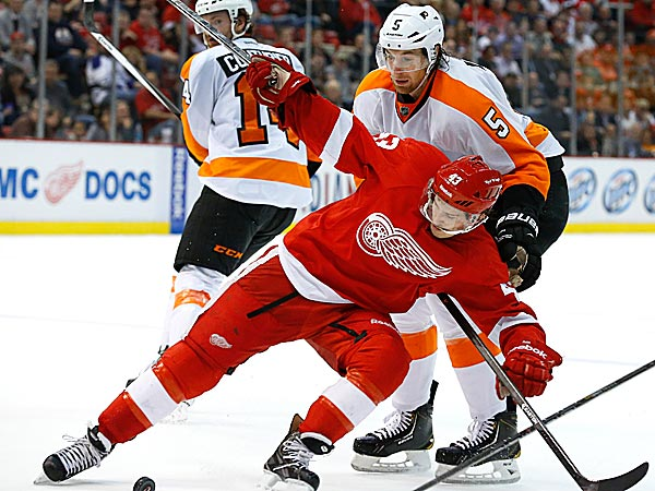 Red Wings center Darren Helm is held by Flyers defenseman Braydon Coburn. (Paul Sancya/AP)