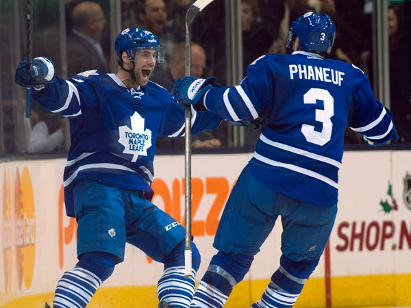 Toronto Maple Leafs center Trevor Smith, left, celebrates his game winning overtime goal with teammate Dion Phaneuf during an NHL hockey game, Thursday, Dec. 5, 2013 in Toronto. (AP Photo/The Canadian Press, Frank Gunn)