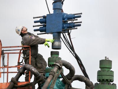A worker cleans and lubricates the head of the machine, after the stimulation hydraulic fracturing of one segment of the well is finished, at Southwestern Energy Co.´s natural gas production site at the Marcellus Shale formation in Camptown, Pennsylvania, U.S., on Wednesday, Oct. 19, 2011. The Marcellus Shale, located in the U.S. Northeast, contains natural gas, which is obtained through hydraulic fracturing, a technique in which millions of gallons of water, sand and chemicals are pumped underground to break apart the rock. Photographer: Julia Schmalz/Bloomberg