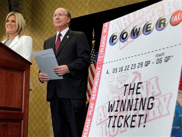 Arizona Lottery Director of Budget, Products and Communications Karen Bach, left, and Arizona Lottery Executive Director Jeff Hatch-Miller stand next to an enlargement of the winning $587.5 Million Powerball ticket, Friday, Dec. 7, 2012 during a news conference in Scottsdale, Ariz. The Lottery held the news conference to announce that the Arizona Lottery Powerball jackpot winning ticket has been claimed by an unidentified Arizona man. The $587.5 million jackpot is the largest in Powerball history and will be shared by co-winners Mark and Cindy Hill from Missouri. (AP Photo/Matt York)