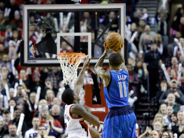 Dallas Mavericks guard Monta Ellis, right, puts up the winning shot at the buzzer as Portland Trail Blazers guard Wesley Matthews defends during an NBA basketball game against the Portland Trail Blazers in Portland, Ore., Saturday, Dec. 7, 2013. Ellis scored 22 points as they beat the Trail Blazers 108-106. (Don Ryan/AP)