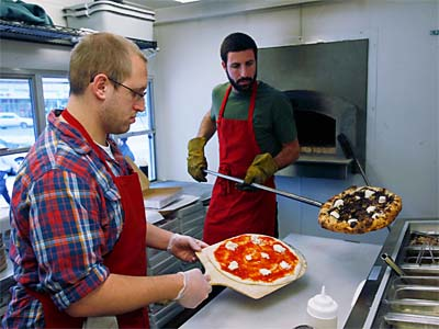 From left, Eric Hilkowitz (left) creates a Margherita pizza as Jonah Fliegelman (right) pulls a Radicchio pizza from the oven at Pitruco. ( MICHAEL S. WIRTZ, Fiule / Staff Photographer )