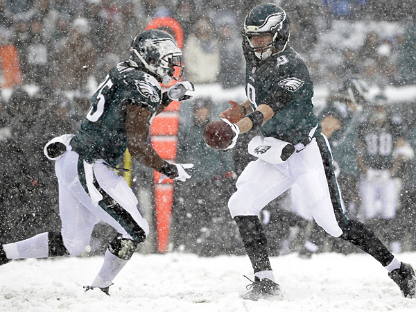 Eagles quarterback Nick Foles (right) hands off to LeSean McCoy during the first half against the Lions. (Matt Rourke/AP)