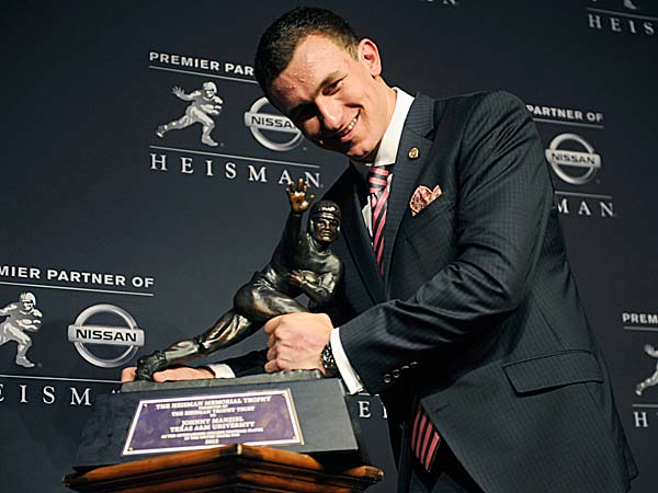 Texas A&M quarterback Johnny Manziel poses with the Heisman Trophy after becoming the first freshman to win the award. (Henny Ray Abrams/AP)