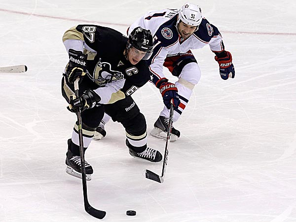 The Penguins´ Sidney Crosby skates around the Blue Jackets´ Fedor Tyutin. (Gene J. Puskar/AP)