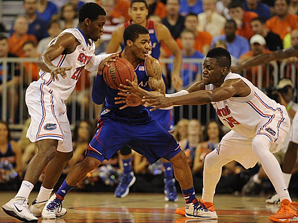 Kansas guard Frank Mason tries to keep the ball with Florida guard Michael Frazier II and Florida forward Will Yeguete try to get possession. (Phil Sandlin/AP)