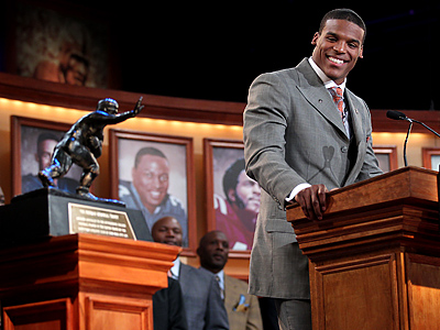 Auburn´s Cam Newton looks at the trophy while he makes his acceptance speech. (AP Photo/Heisman Trophy Trust, Kelly Kline)