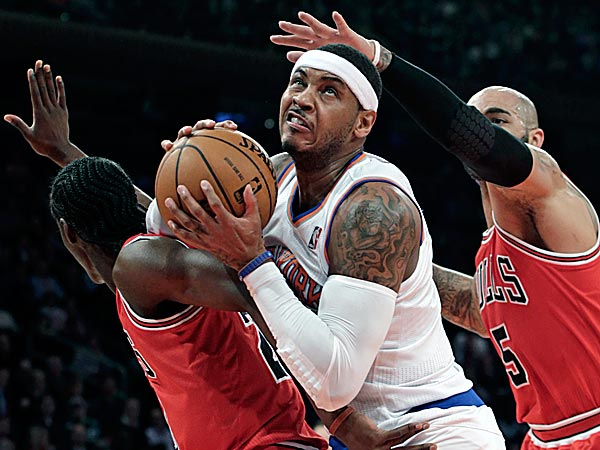 Bulls forwards Taj Gibson and Carlos Boozer smother Knicks forward Carmelo Anthony who tries to free himself from their defense. (Kathy Willens/AP)