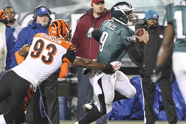 Under pressure, Eagles quarterback Nick Foles runs for  a first down before the Bengals´ Michael Johnson pushes him out of bounds in the second quarter at Lincoln Financial Field, December 13, 2012.  (David M Warren/Staff Photographer)