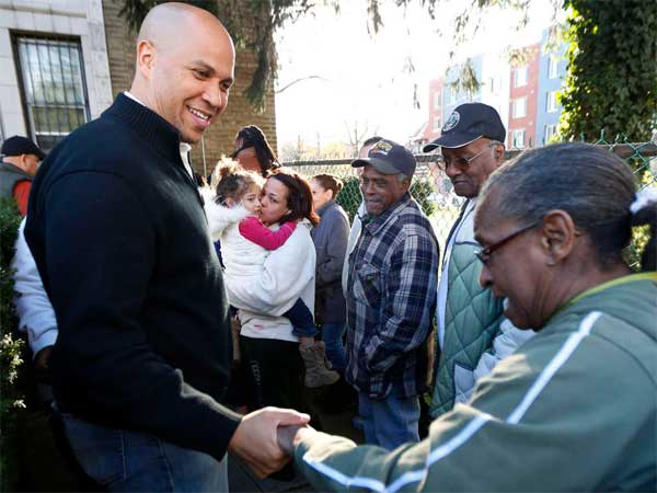 Newark, N.J., Mayor Cory Booker shakes hands with Grace Harris as she waits at a community center for donated clothing. (Julio Cortez / Associated Press)