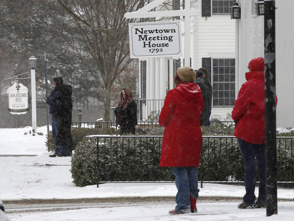 People pause in silence while church bells ring in honor of the victims of the Sandy Hook massacre, Saturday, Dec. 14, 2013, in Newtown, Conn.  Newtown is asking that people honor the victims one the one-year anniversary in ways that are quiet and personal. (AP Photo/Robert F. Bukaty)