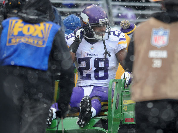 Vikings running back Adrian Peterson is carted off the field after injuring his ankle on a play in the second quarter of an NFL football game against the Baltimore Ravens, Sunday, Dec. 8, 2013, in Baltimore. (Gail Burton/AP)