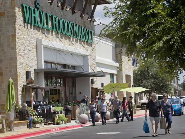 Whole Foods Market, headquartered in Austin, Texas, plans to add more than 30 stores this year, a record for the chain. But even as it expands it faces challenges from other grocers such as Trader Joes. Customers enter one of the chain´s stores in Austin in 2012. (Laura Skelding / Austin American-Statesman / MCT)