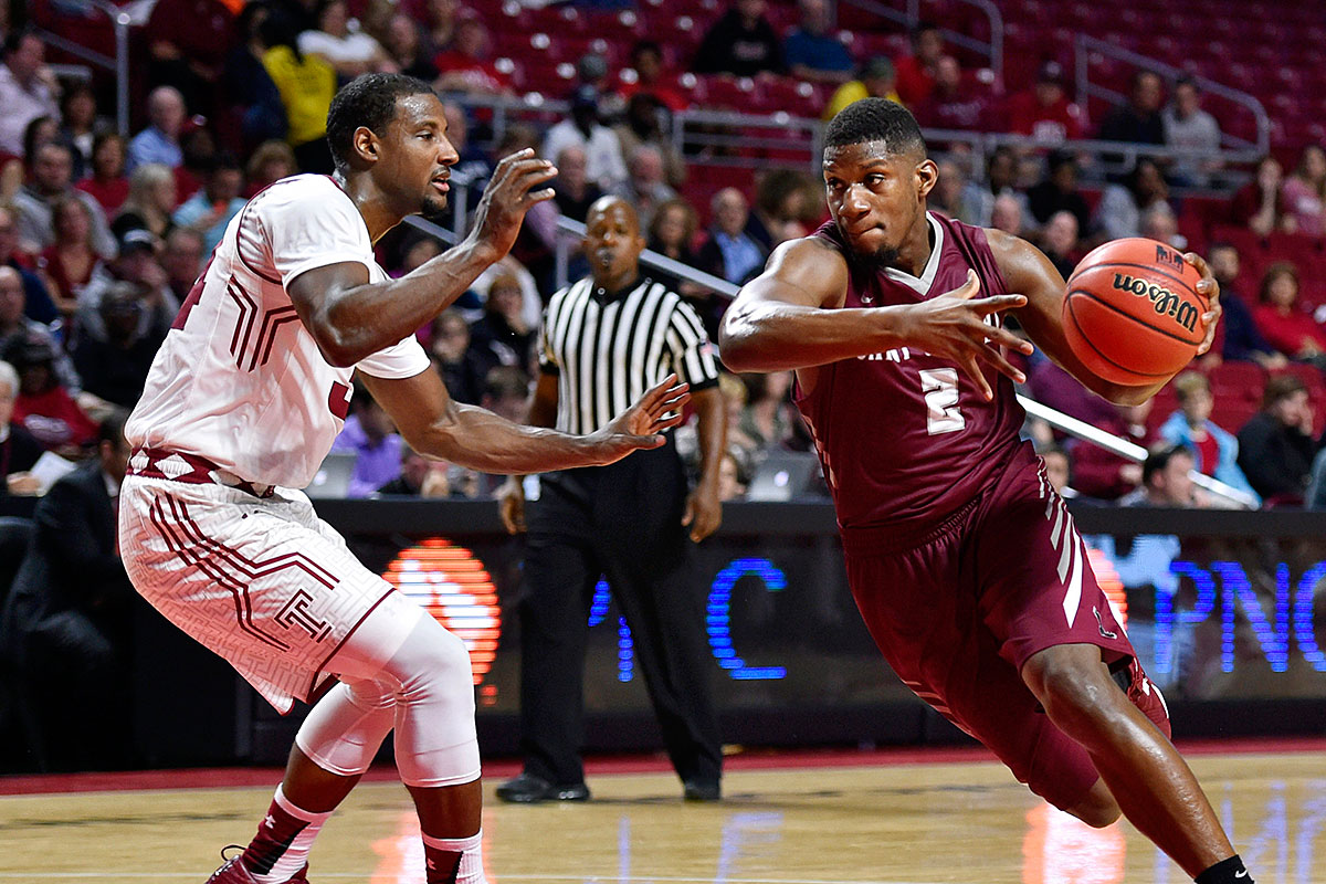 Saint Joseph´s Hawks guard Aaron Brown (2) dribbles past Temple Owls guard Devin Coleman (34) during the first half at Liacouras Center.