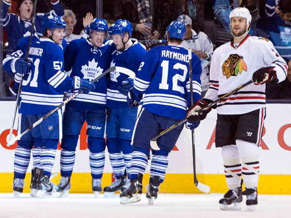 Maple Leafs´ Peter Holland, center, is congratulated by teammates after scoring against the Chicago Blackhawks during the first period of an NHL hockey game in Toronto on Saturday, Dec. 14, 2013. (AP Photo/The Canadian Press, Chris Young)