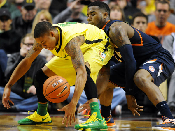 Oregon guard Joseph Young, left, and Illinois guard Rayvonte Rice scramble for a loose ball during the first half of an NCAA college basketball game in Portland, Or., Saturday, Dec. 14, 2013. (Steve Dykes/AP)