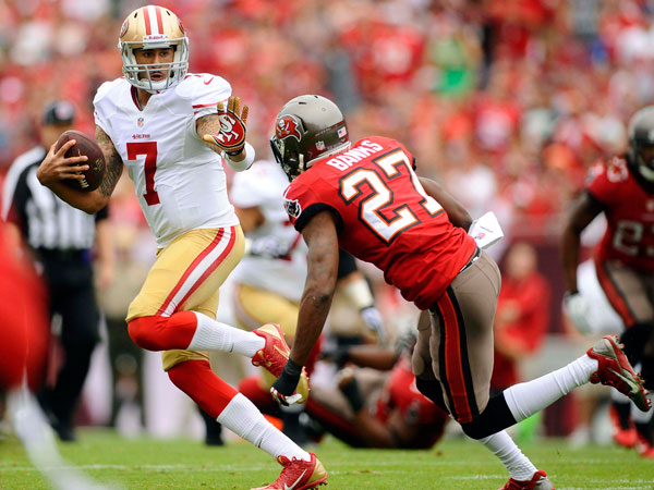 49ers quarterback Colin Kaepernick (7) eludes Tampa Bay Buccaneers cornerback Johnthan Banks (27) on a run during the first quarter of an NFL football game Sunday, Dec. 15, 2013, in Tampa, Fla. (Brian Blanco/AP)