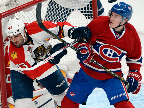 Canadiens right wing Brendan Gallagher (11) and Florida Panthers defenseman Mike Weaver (43) battle in front of the net during first-period NHL hockey action on Sunday, Dec. 15, 2013, in Montreal. (AP Photo/The Canadian Press, Ryan Remiorz)