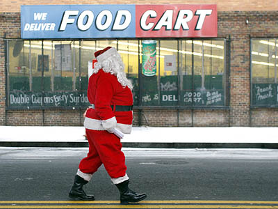 Willam Knellinger, dressed as Santa, waits in the middle of the street to pass out fliers for a furniture store along the snowy 2400 block of Kensington Avenue in Philadelphia on Thursday. (David Maialetti / Staff Photographer)